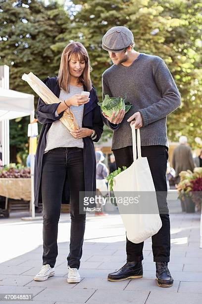Full length of couple using mobile phone while shopping vegetables in market