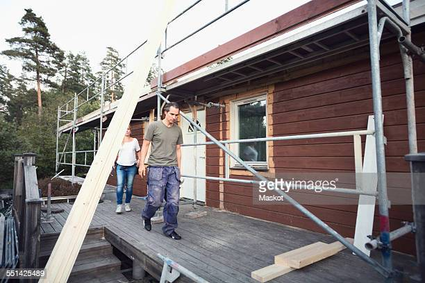 Full length of couple walking on floorboard of house being renovated