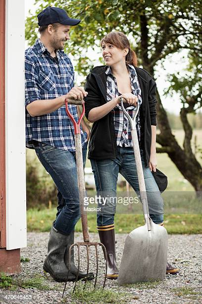 Full length of couple with pitchfork and shovel on farm