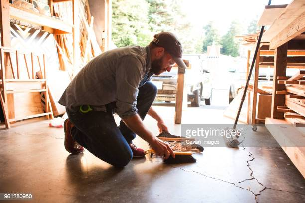 full length of craftsperson cleaning wooden shavings on floor at workshop - sweeping stock pictures, royalty-free photos & images