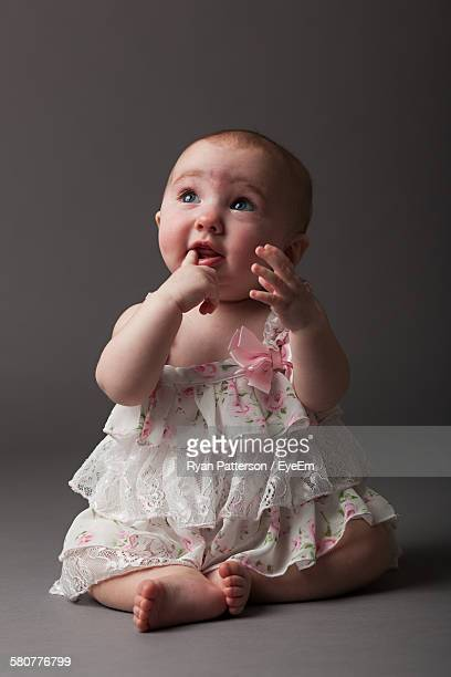 Full Length Of Cute Baby Girl Sitting Against Gray Background
