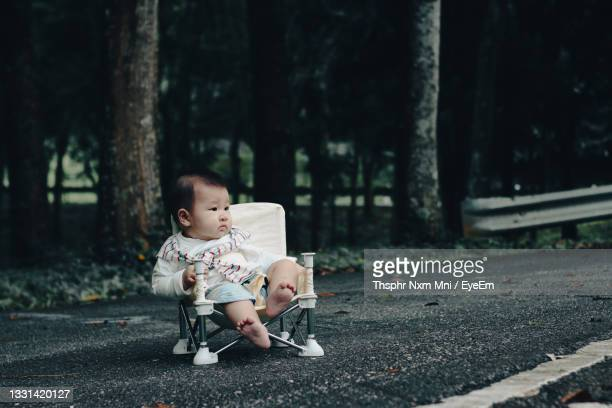 full length of cute baby girl sitting on floor - unknown gender stock pictures, royalty-free photos & images