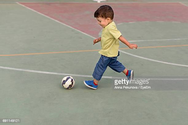 Full Length Of Cute Boy Playing Soccer