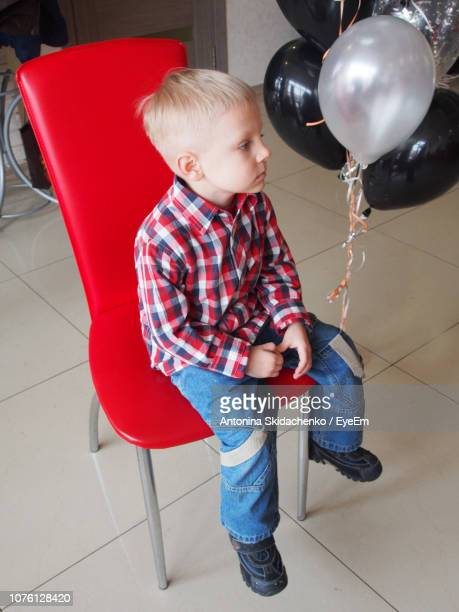 Full Length Of Cute Boy With Helium Balloons Sitting On Red Chair At Home