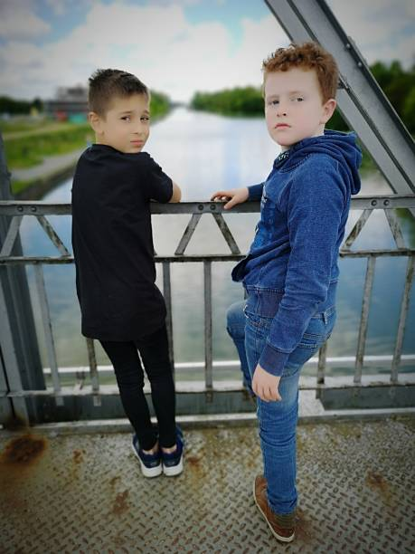 Full Length Of Cute Brothers Standing On Footbridge Over River