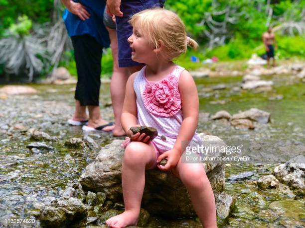 full length of cute girl looking away while sitting on rock by stream - 背景に人 ストックフォトと画像