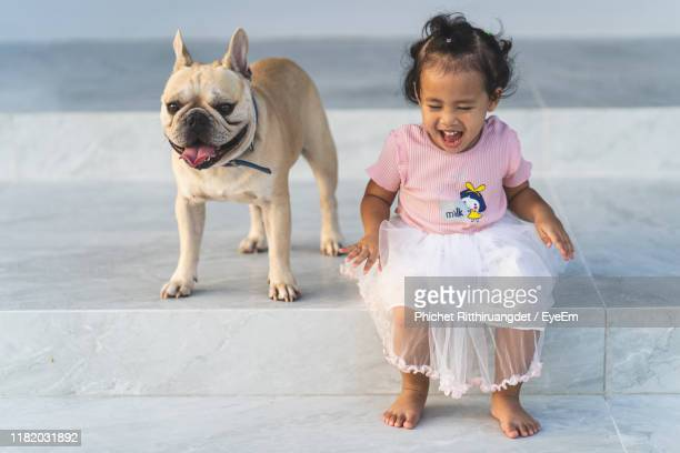full length of cute girl sitting by dog - phichet ritthiruangdet stock photos and pictures