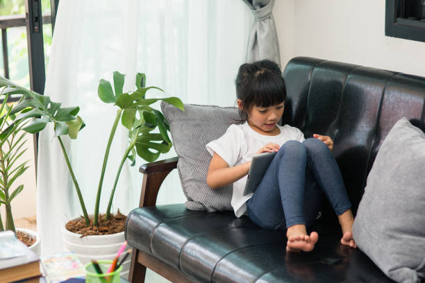 Full Length Of Cute Girl Using Digital Tablet While Sitting On Sofa At Home