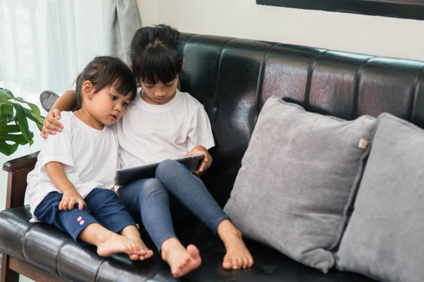 Full Length Of Cute Sisters Using Digital Tablet While Sitting On Sofa At Home