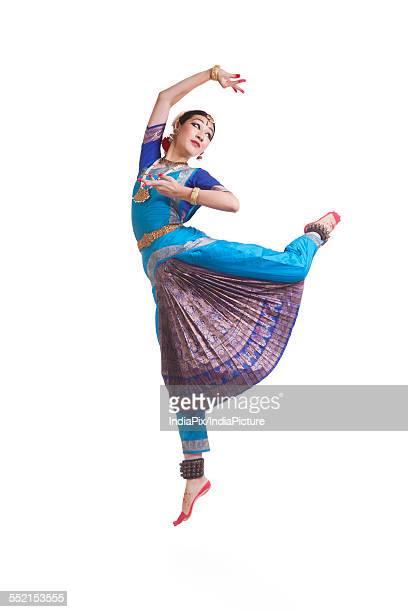 Full length of dancer performing Bharatanatyam against white background