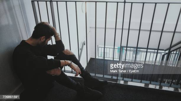 full length of depressed man sitting by railing in building - one man only stock pictures, royalty-free photos & images