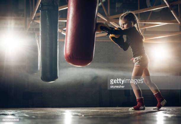 Full length of determined little girl punching a bag on kickboxing training.
