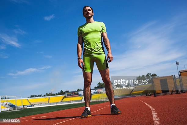 Full length of determined male athlete standing on race track
