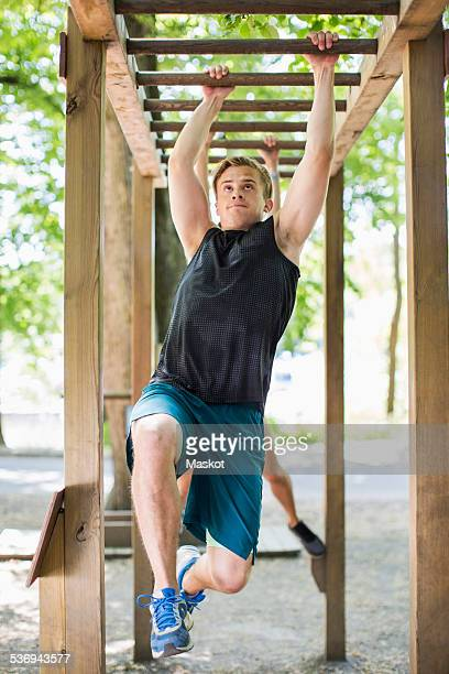 Full length of determined man hanging on monkey bars at outdoor gym