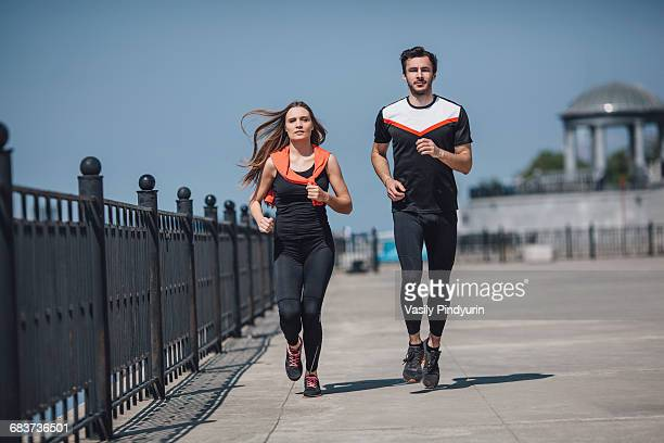 Full length of determined people running on promenade against clear sky