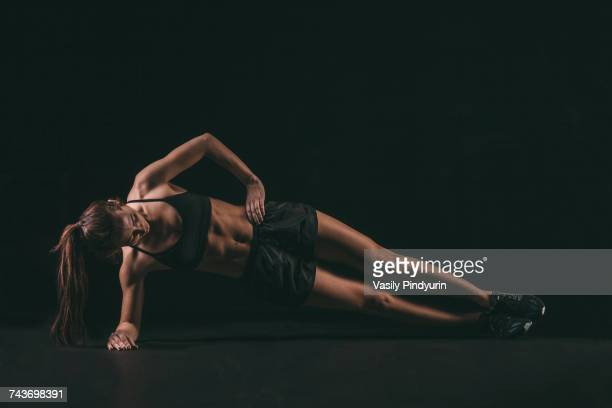 Full length of determined woman doing side plank exercise against black background