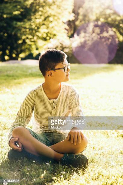 Full length of disabled boy sitting on grassy field during sunny day