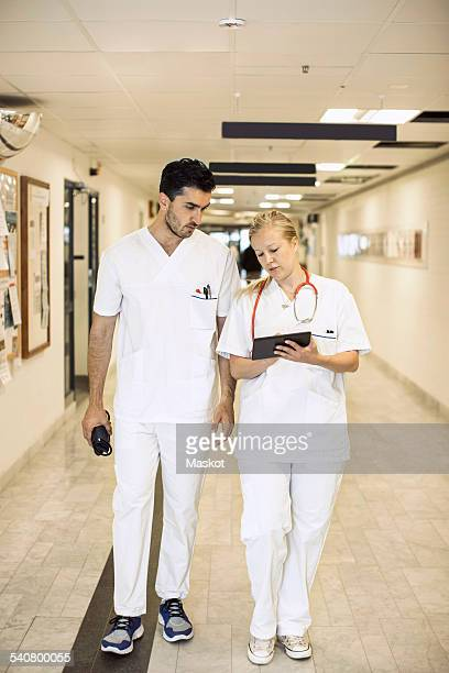 Full length of doctors discussing over digital tablet in hospital corridor