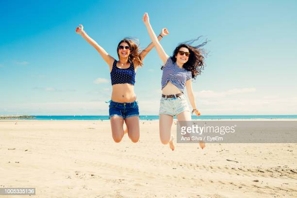 full length of excited female friends jumping at beach during sunny day - ピレネーアトランティーク ストックフォトと画像