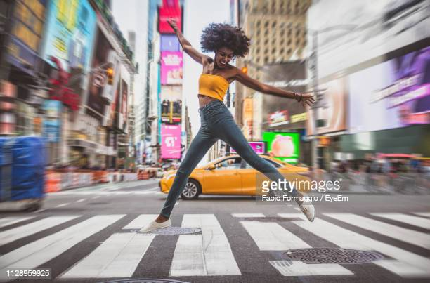 full length of excited young woman dancing on zebra crossing in city - 22 jump street fotografías e imágenes de stock