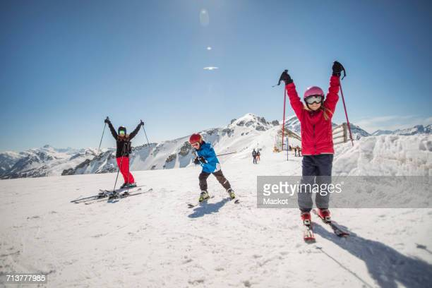 Full length of family enjoying while skiing against clear sky