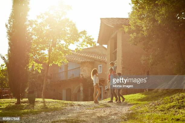 full length of family standing against houses - scena non urbana foto e immagini stock