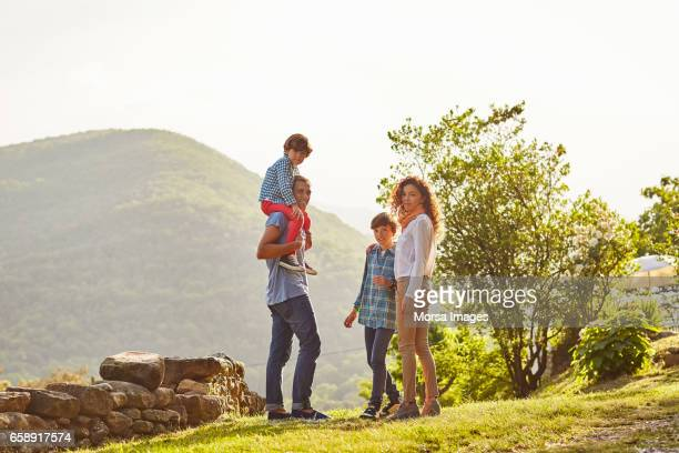 full length of family standing on grassy field - mid distance stock pictures, royalty-free photos & images