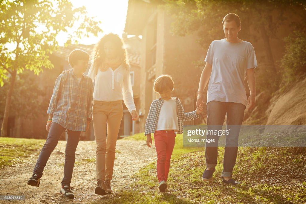 Full length of family walking against houses : Stock Photo