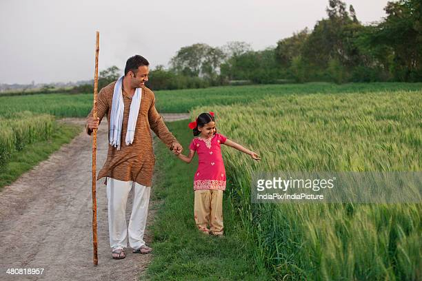 Full length of farmer and daughter standing in wheat field