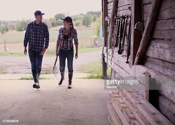 Full length of farming couple walking in barn