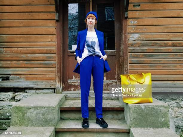 full length of fashionable woman standing against house - blue suit stock pictures, royalty-free photos & images