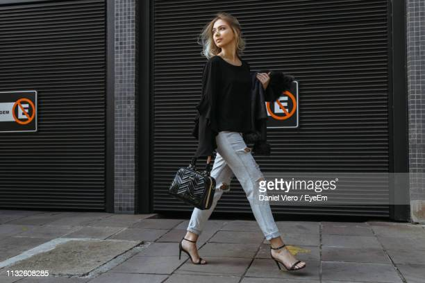 full length of fashionable woman walking on footpath - fashionable stock pictures, royalty-free photos & images
