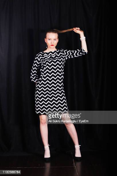 full length of fashionable young woman standing against black curtain - striped dress stock pictures, royalty-free photos & images