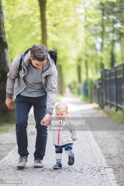full length of father and son holding hands while walking on footpath - stay at home father stock pictures, royalty-free photos & images