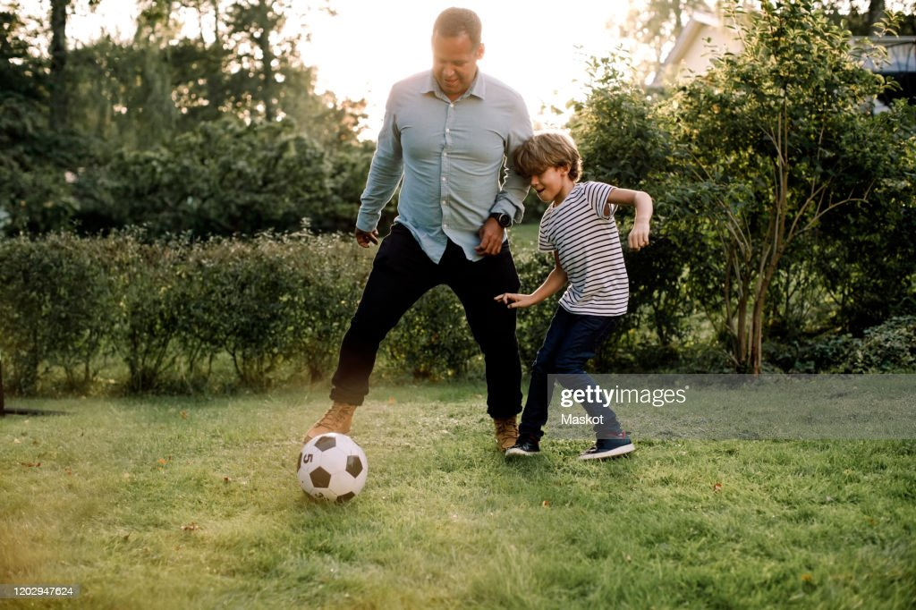 Full length of father and son playing soccer in backyard during weekend activities : Stock-Foto