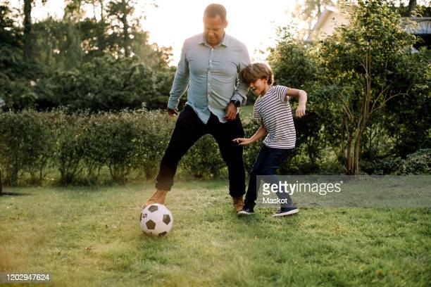 full length of father and son playing soccer in backyard during weekend activities - playing stock-fotos und bilder