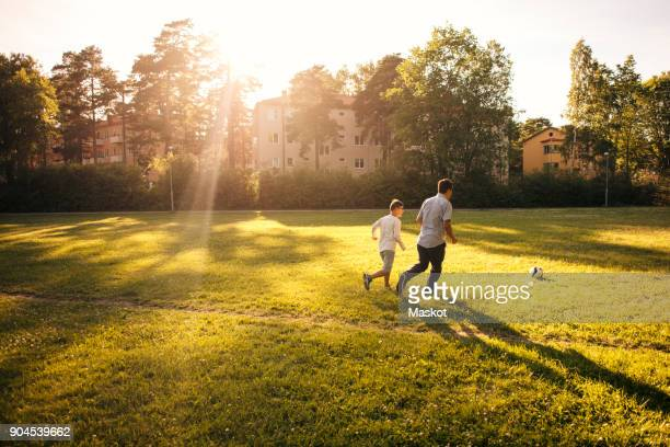 Full length of father and son playing soccer on grassy field during sunny day