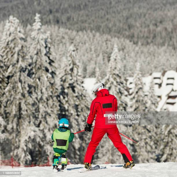 full length of father and son skiing on snow during winter - ski pole stock pictures, royalty-free photos & images
