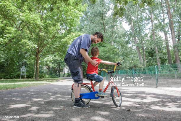 full length of father and son with bicycle at park - leanintogether stock pictures, royalty-free photos & images