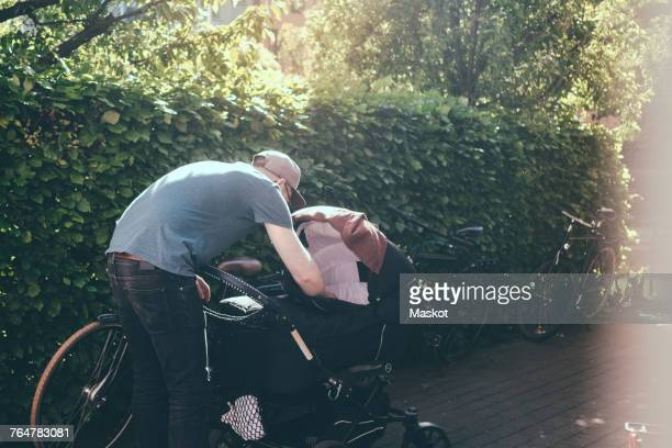 full length of father bending over baby carriage on footpath at park during sunny day - bent over babes stock pictures, royalty-free photos & images