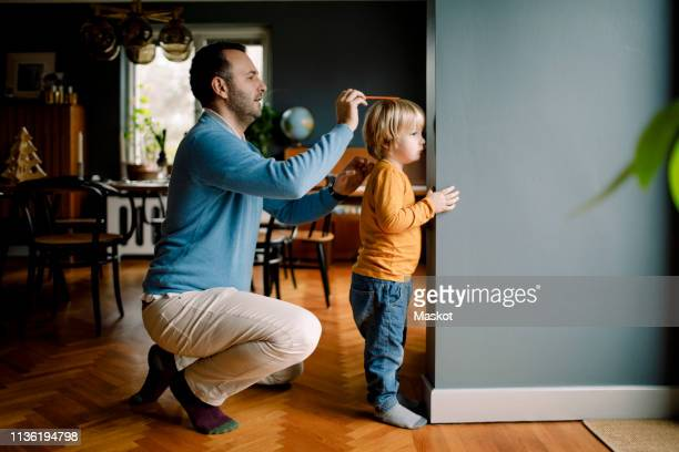 full length of father measuring daughter's height against wall at home - medir imagens e fotografias de stock