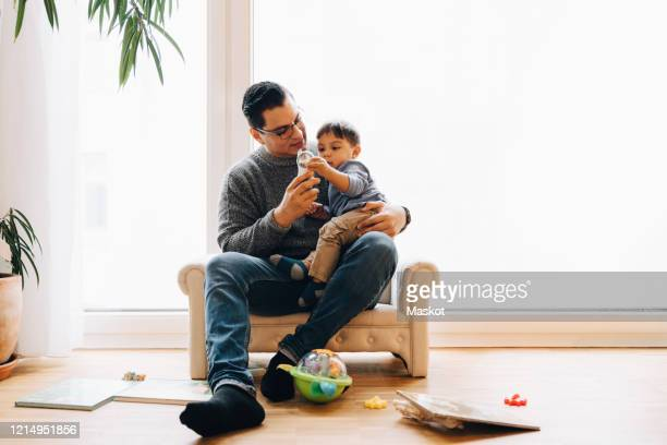 full length of father playing with toddler son while sitting on sofa at home - paternity leave stock pictures, royalty-free photos & images