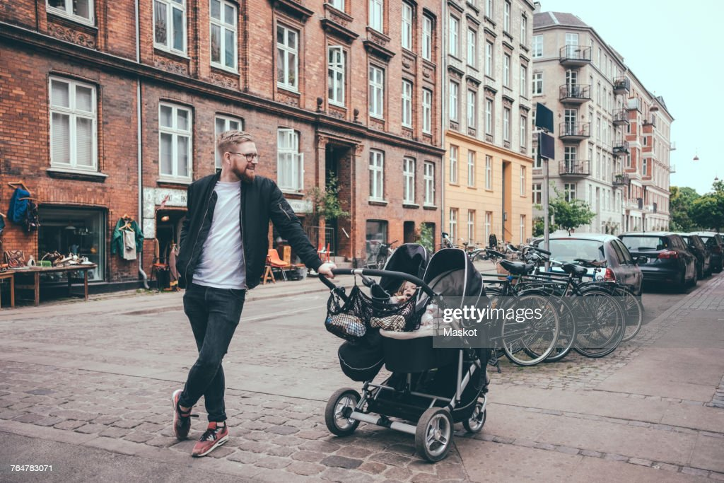 Full length of father standing by baby carriage on street in city : Stock-Foto