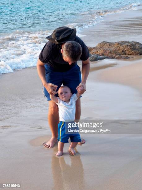 full length of father with baby boy standing on shore at beach - monika gregussova stock pictures, royalty-free photos & images