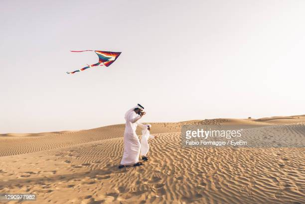 full length of father with son flying kite in desert - desert stock pictures, royalty-free photos & images