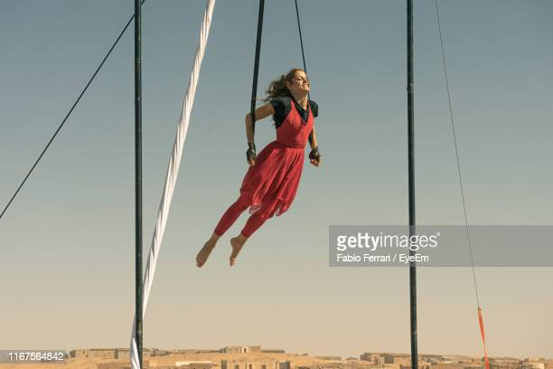 full length of female aerial dancer dancing while hanging from textile against sky - 空中曲芸師 ストックフォトと画像