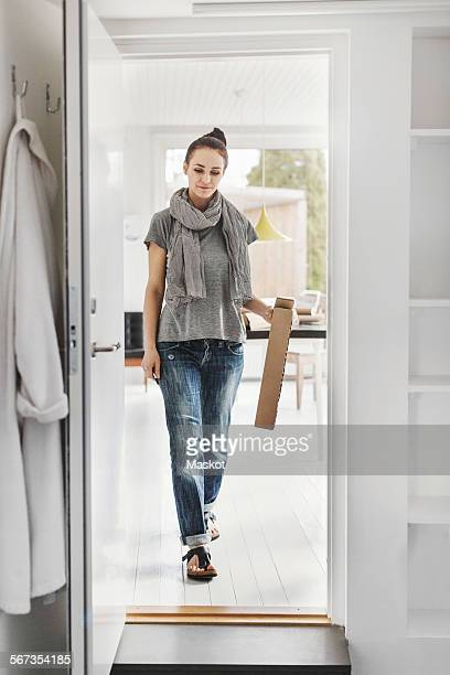 Full length of female architect walking towards doorway at home