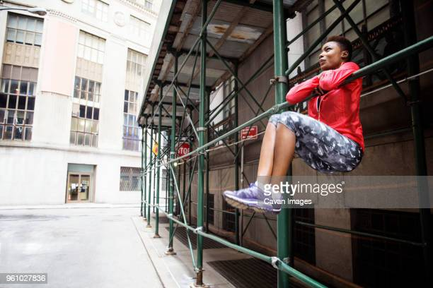 full length of female athlete hanging on metal rod by city street - center athlete stock pictures, royalty-free photos & images