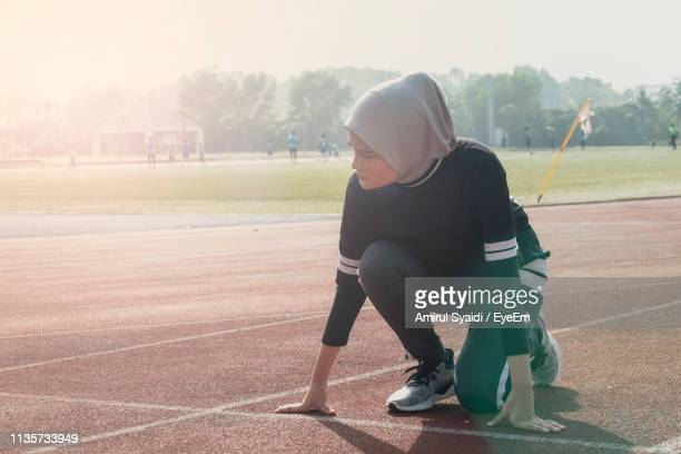 full length of female athlete kneeling on track - athlete stock pictures, royalty-free photos & images