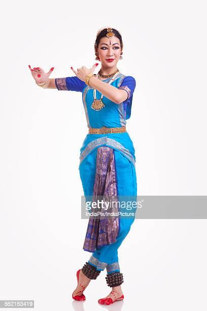 Full length of female Bharata Natyam performer over white background
